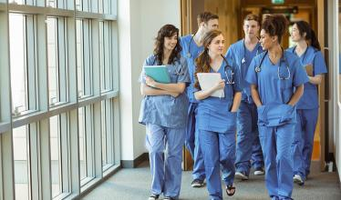 Several medical students wearing blue scrubs walk in a hallway.