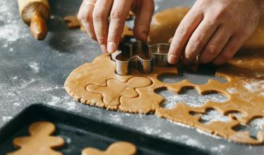 Hands cutting gingerbread cookies