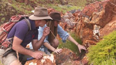 Astrobiologists Martin Van Kranendonk and Tara Djokic examine the fossilized remains of an ancient hot spring in the Pilbara region of Australia.