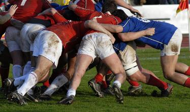 Rugby players in white shorts and either blue or red shirts push against each other during a match.
