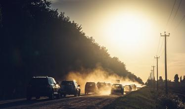cars kicking up dust on a road