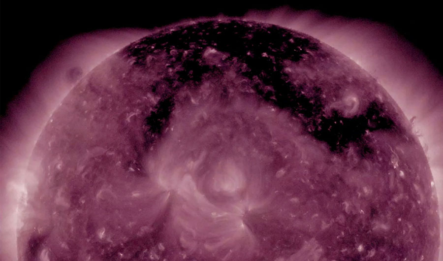 An ultraviolet image of the sun, showcasing a pi-shaped coronal hole across its surface.
