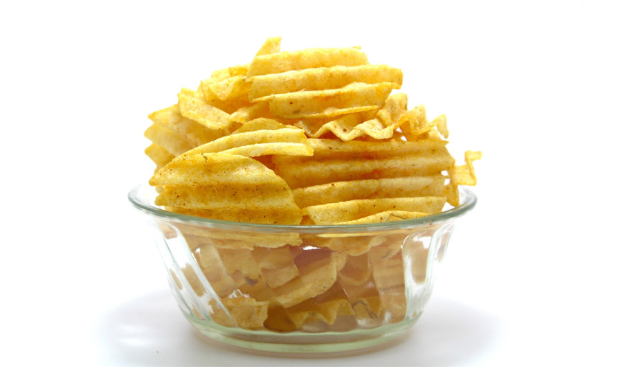 Glass bowl of potato chips.