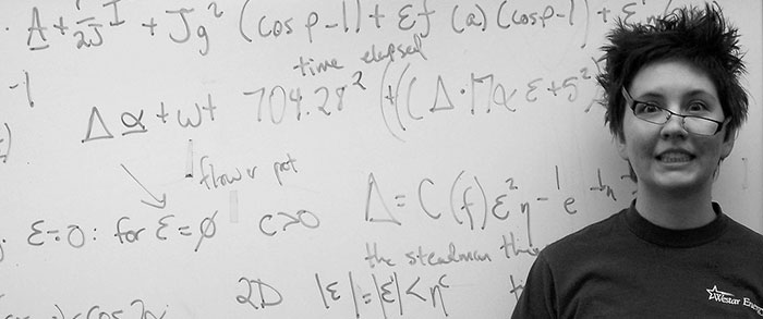 Closeup of person with bushy hair and titled glasses making goofy expression while standing in front of a whiteboard full of equations.