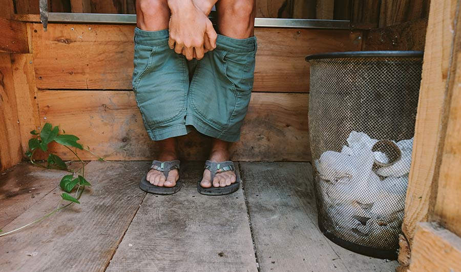 Barefoot person pulling down pants in outhouse (cropped from shins).