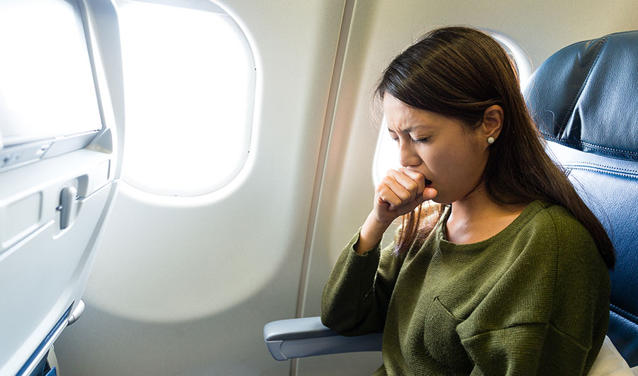 Woman coughing into hand seated by airplane window.,