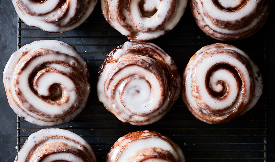 A picture of freshly baked cinnamon rolls taken from above, with white icing atop browned, coiled rolls.