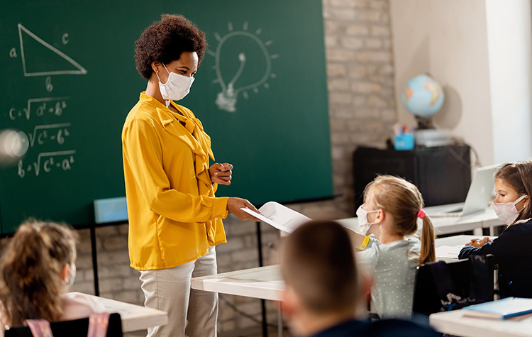 A teacher, wearing a mask, stands near a student, also wearing a mask, in a classroom