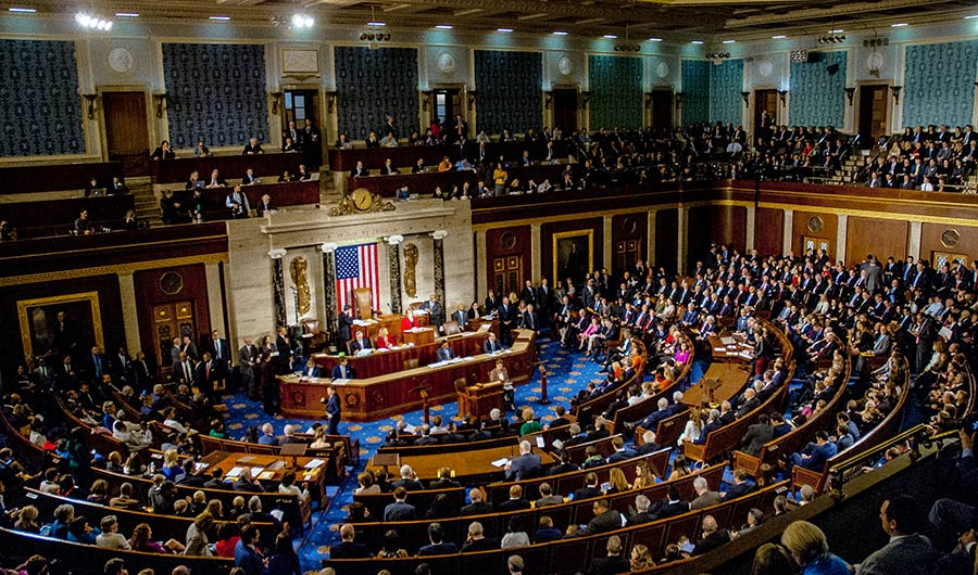 An image of people collected on the floor of the House of Representatives.