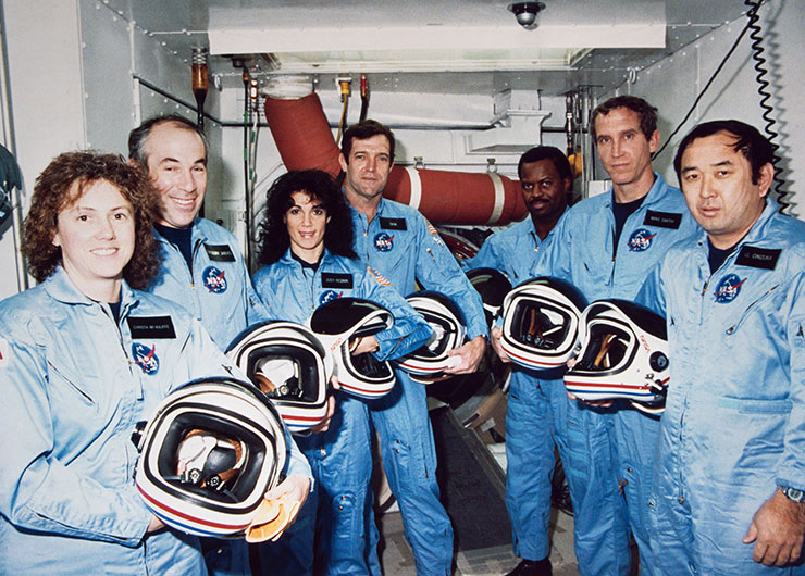 Crew of STS-51L, wearing blue suits and holding helmets.