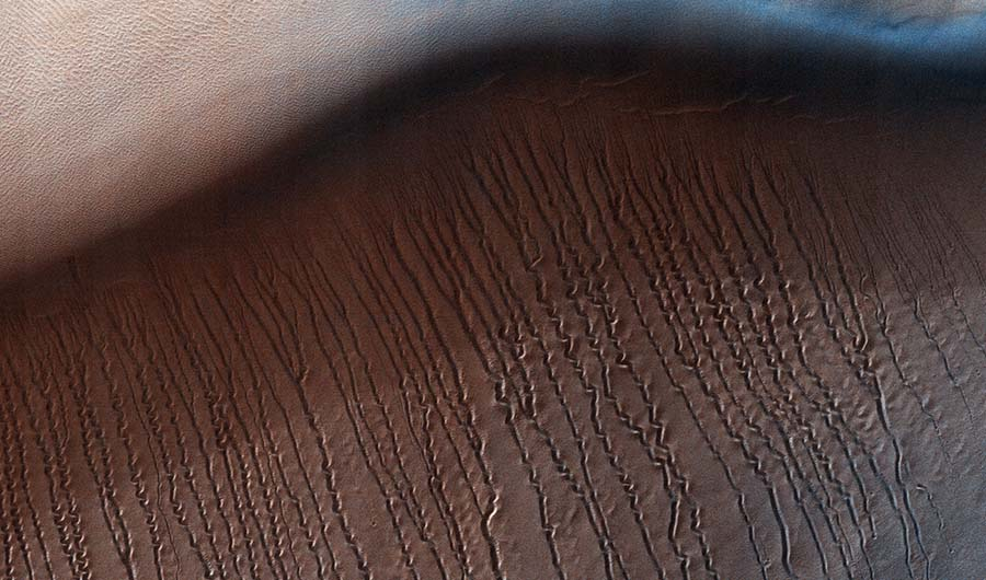 A birds-eye photo of a small central section of the Hellas Planitia basic, on Mars. Myriad scratch marks are etched into the dunes.