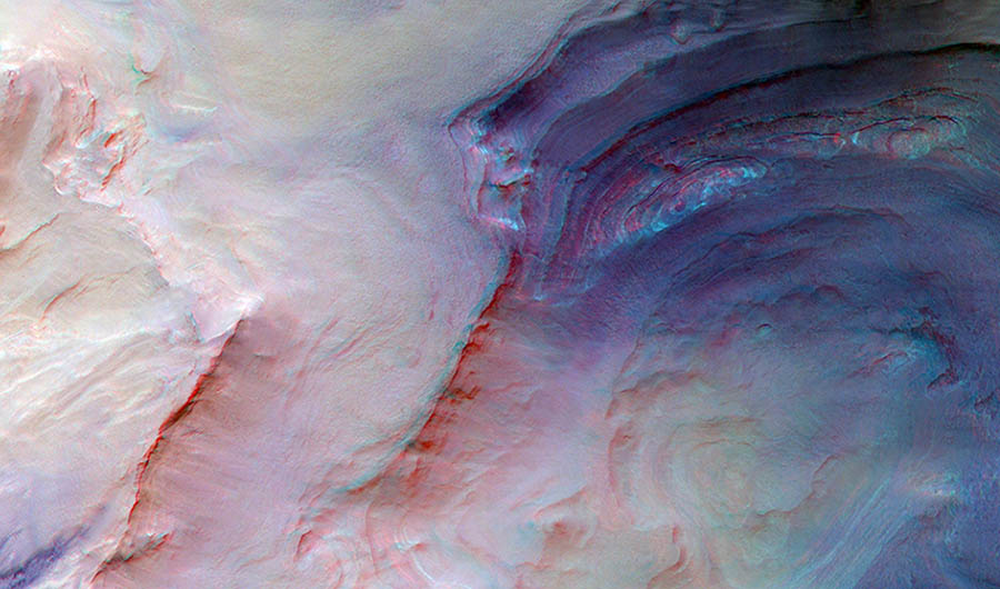 A picture of the Hellas basin on Mars, as seen from orbit. The picture itself is overlaid with hues of pink, green, and blue, highlighting the cragginess of the landscape.