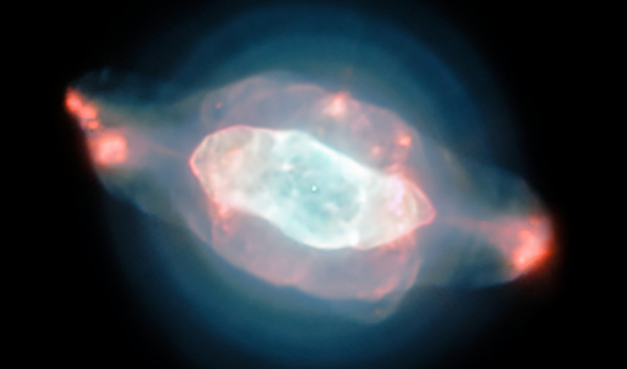 Nebula NGC 7009, depicted in pale hues of blue and pink. This nebula is also known as the Saturn Nebula for its striking visual similarity to the appearance of Saturn and its rings.