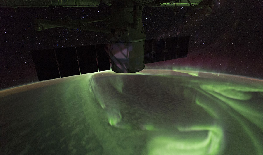 The Southern Lights as photographed from the ISS. The aurora glows green across the atmosphere, while the ISS floats above the earth.