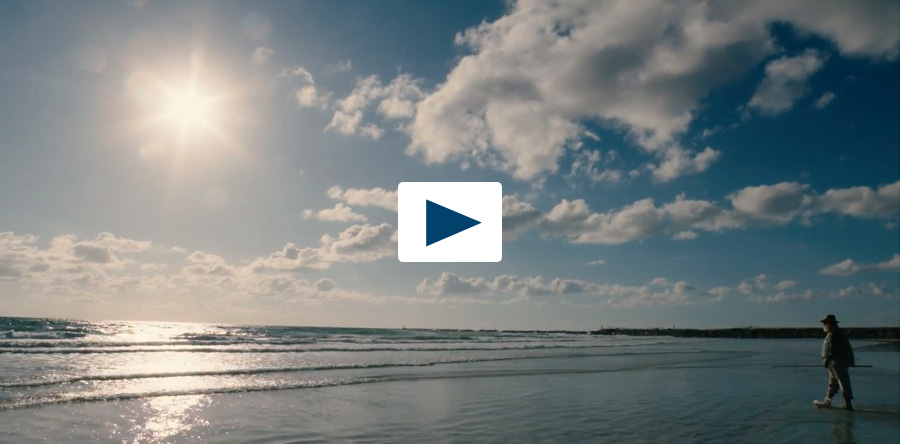 Still image of sunlit beach, taken from a video