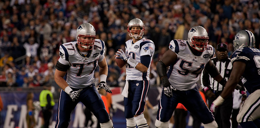 New England Patriots quarterback Tom Brady stands behind two blockers while a Dallas Cowboy rushes toward him, as a referee watches.