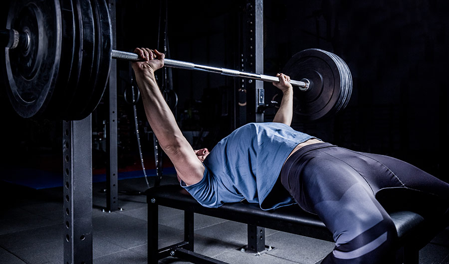 In a darkened room, a man in a blue tee shirt lies down on a bench and pushes a heavy barbell above his head.