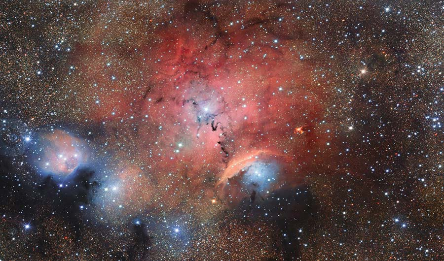 This is Sharpless 29, shown as a red plume of space dust across a background of stars.