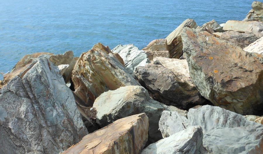 Large, dark, angular boulders atop a cliff above the sea.