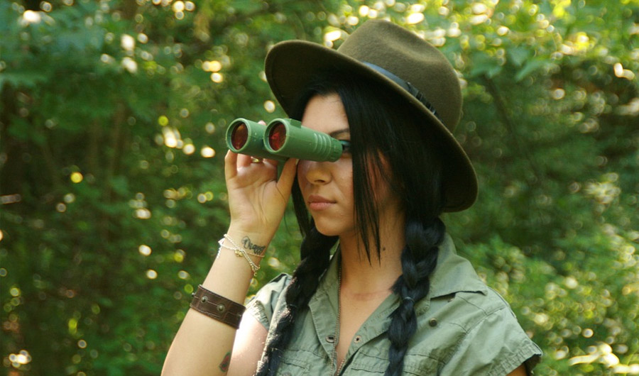 Girl with binoculars in forest