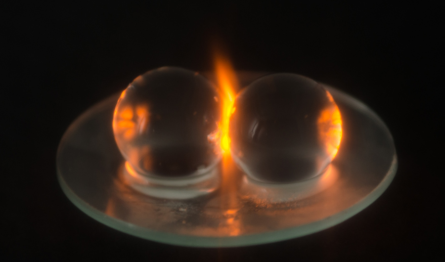 The image shows two clear, water-filled balls sparking while they are being microwaved.