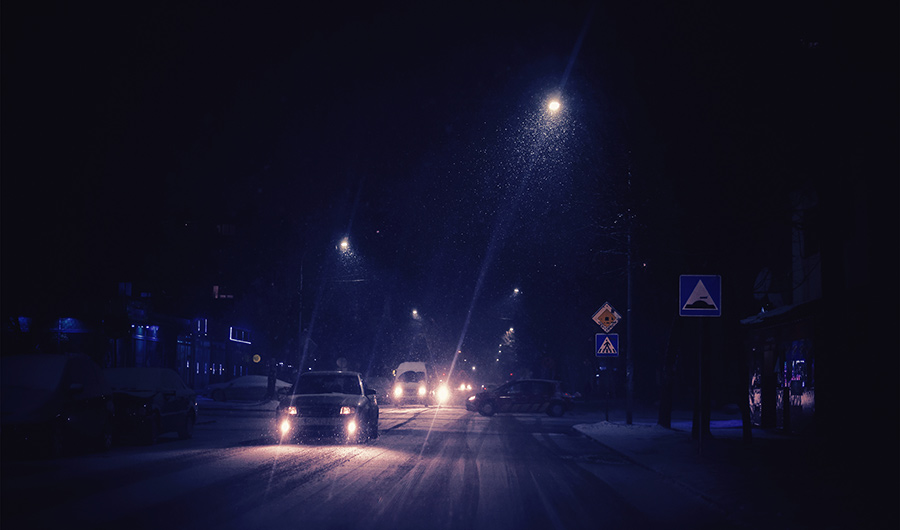 Picture of a city intersection at night, as snow falls and cars travel along the roads.