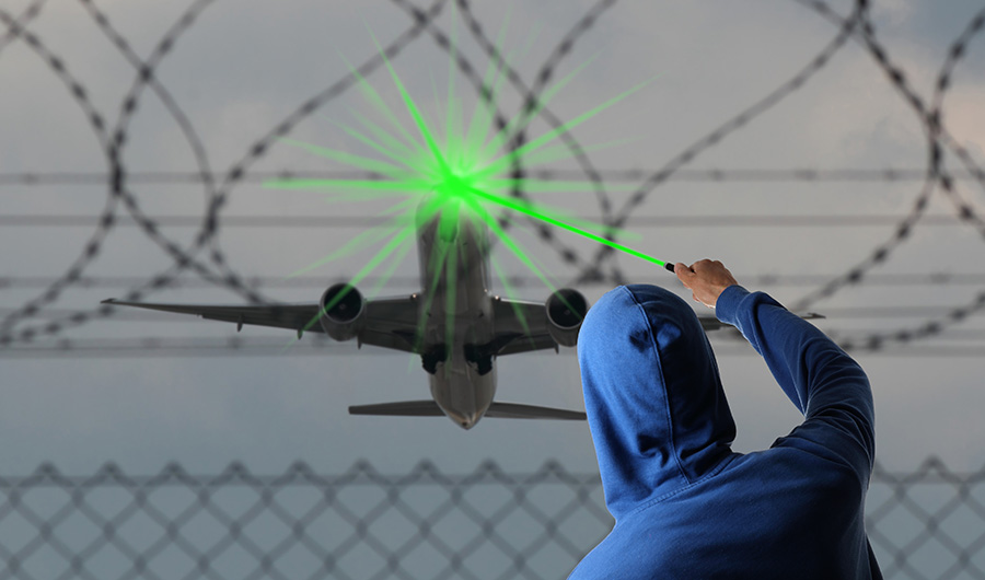 Person standing by a barbed wire fence with their back to the camera is pointing a green laser at an airplane in flight.