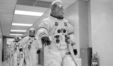 Apollo 13 astronauts Lovell, Swigert, and Haise walk towards the transfer vans in their astronaut suits.