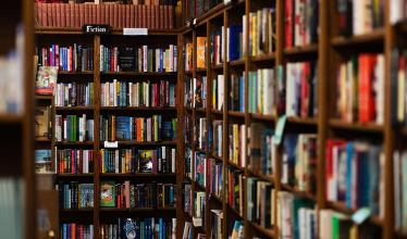A full bookshelf in a book store, in the Fiction section.