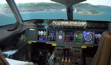 The image shows a flight simulator with a cockpit with controls, as well as a set of screens with a pilot's view of the plane's surroundings.