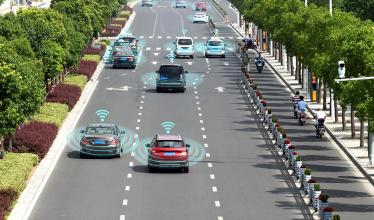 Image shows busy road with cars emitting signals to each other to assist with self driving.