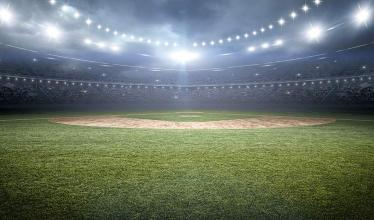 Image of a baseball stadium lit by floodlights at night
