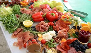 Wide array of multi colored foods on a table, including peppers, herbs, tomatoes, cured meats and more.