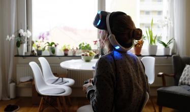 Girl wearing a VR headset and facing away from the camera looks up while a window backlights the scene.