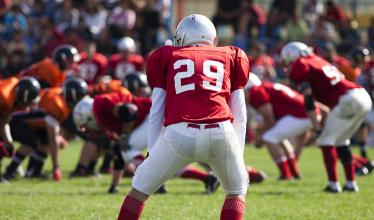 Image shows a player, crouched with his back to the camera, facing a field full of football players.