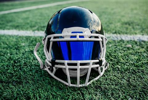 Football helmet with a visor atop a grassy football field