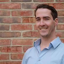 portrait of writer Joshua Learn, posed with a brick wall behind him. Learn has dark hair and is wearing a blue shirt.